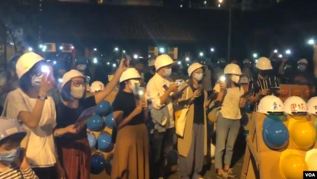 300多名蒙面的集会参加者在25号(星期五)晚上8点左右在九龙土瓜湾的牛棚艺术村空地上聚集,出席香港艺术家与当地社区合作举办的艺术展览开幕仪式。