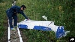 Một nhân viên của trạm nước xem xét mảnh lớn còn sót lại sau vụ tai nạn của máy bay MH17 ở làng Hrabove, miền đông Ukraine.