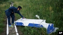 Seorang petugas perairan setempat memeriksa sebuah kepingan pesawat Malaysia Airlines MH17 yang masih tergeletak di lokasi jatuhnya pesawat dekat desa Hrabove, Ukraina timur (14/7).