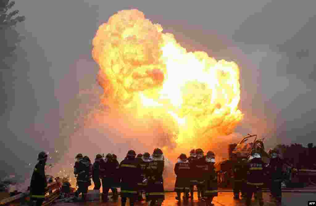 Firefighters work to put out a fire as white phosphorus exploded after a violent collision when a truck crashed into another vehicle on a highway in Wuhan, central China's Hubei province. One of the two truck drivers was killed in the accident while the other succeeded to get out of the truck before the explosion.