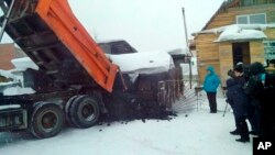 Yelena Salnikova, in a blue jacket, a nurse from a small town of Berezovskiy, Russia, gets a truck full of coal from authorities in the Kemerovo coal-rich region for losing 30 kilos (66 pounds) in weight, Dec. 23, 2015.