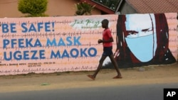 A young boy walks past a wall with graffiti urging people to wear face masks in Harare, May, 28, 2020. Manhunts have begun after hundreds of people fled quarantine centers in Zimbabwe and Malawi.