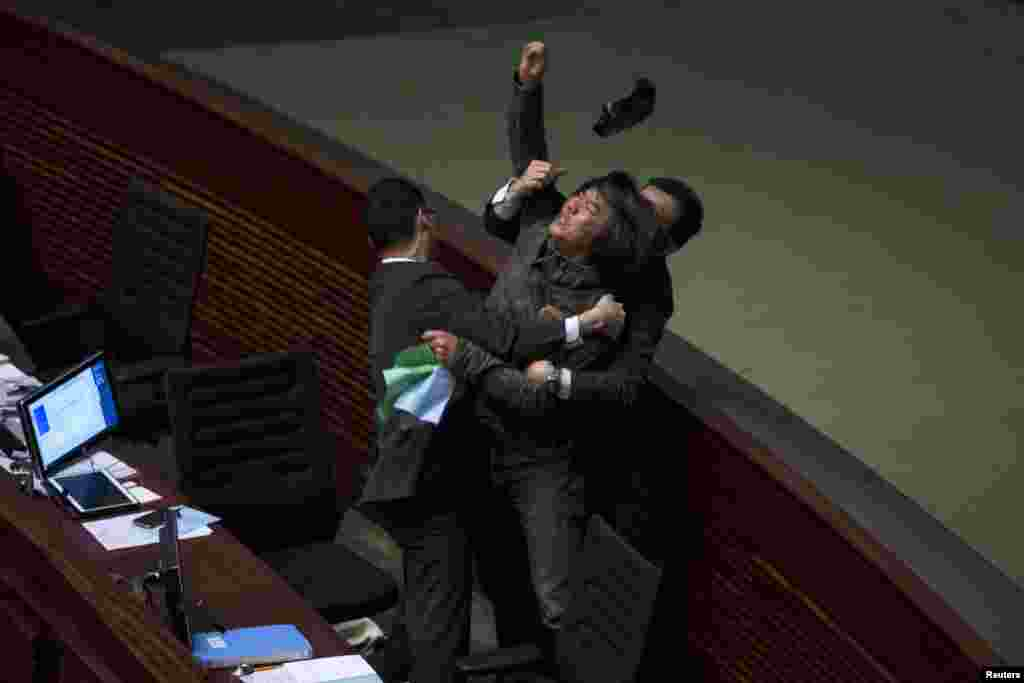 Pro-democracy lawmaker Leung Kwok-hung throws an object at Hong Kong's Financial Secretary John Tsang (not pictured) to demand a universal retirement protection scheme during the annual budget report meeting at the Legislative Council in Hong Kong.