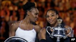2017年1月28日,美国的塞雷娜·威廉姆斯(小威,右),在墨尔本澳网女子单打决赛中,战胜姐姐维纳斯·威廉姆斯(大威,左)。图为胜后小威手抱奖杯,接受姐姐大威和观众祝贺。