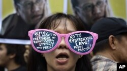A protester, wearing sunglasses with slogans, stands in front of picture of Philippine President Benigno Aquino III during a rally against the anti-cybercrime law in front of the Supreme Court in Manila, Philippines, October 9, 2012.