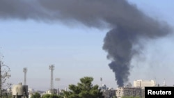 Black smoke billows after a bomb exploded at a military site near a hotel used by United Nations monitors in Damascus, Syria, August 15, 2012.