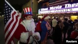 2014年12月24日加利福尼亚: 身着圣诞老人服装的马特·奥恩斯坦手持美国国旗排队买票看午夜放映的《采访》