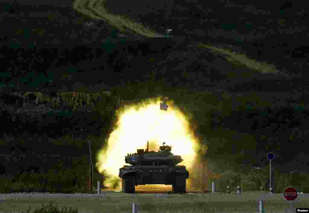 A T-72 tank, operated by a crew from Kazakhstan, fires at a target during the Tank Biathlon competition, part of the International Army Games 2016, at a range in the settlement of Alabino outside Moscow, Russia.