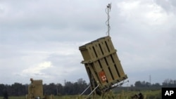 "Israeli soldiers stand next to an ""Iron Dome"" short-range missile defence system after it was deployed near the costal city of Ashkelon on April 4, 2011"