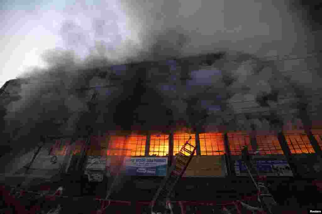 Locals and fire-fighters try to control a fire at a garment factory in Dhaka, Bangladesh. But no one was in the building at the time of fire and there were no casualties, a police official said.