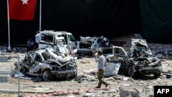 A man walks among the wreckage of vehicles as Turkish rescue workers and police inspect the blast scene following a car bomb attack on a police station in the eastern Turkish city of Elazig, Aug. 18, 2016. The explosion, blamed by Defense Minister Fikri Isik on the outlawed Kurdistan Workers' Party (PKK), happened in the garden of the four-storey building in Elazig.