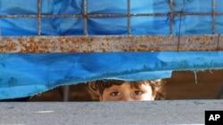 Một bé gái Syria nhìn ra ngoài hàng rào trại tị nạn Yayladagi ở Hatay, một tỉnh nằm trong vùng biên giời Thổ Nhĩ Kỳ-Syria