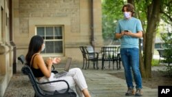 In this photo, Bryan Maley, right, a grad student, interviews a student on campus about mask-wearing experiences as part of a public health survey, Friday, July 30, 2020, in Ithaca, N.Y. (Jason Koski/Cornell University via AP)