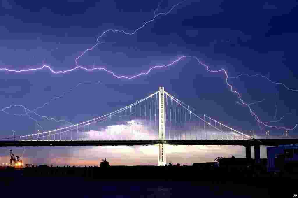 រន្ទះបាញ់កើតឡើងនៅលើស្ពាន San Francisco-Oakland Bay Bridge ខណៈដែលព្យុះបោកបក់កាត់ក្រុង Oakland រដ្ឋ California សហរដ្ឋអាមេរិក។