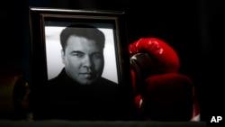 ARSIP – Sebuah potret Muhammad Ali diperagakan di saming sepasang sarung tinju pada Festival I Am Ali di Louisville, Kentucky, 8 Juni 2016 (foto: AP Photo/David Goldman)