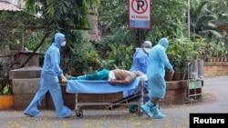 အိႏၵိယႏိုင္ငံ Mumbai ၿမိဳ႕က ေဆးရံု၀န္းတခုမွာ COVID-19 လူနာတဦးကို သယ္ေဆာင္ေနတဲ့ က်န္းမာေရး ၀န္ထမ္းတခ်ိဳ႕။ (ဧၿပီ ၁၁၊ ၂၀၂၀)