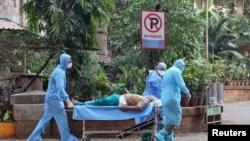 Médicos transportam doente num hospital de Mumbai, Índia