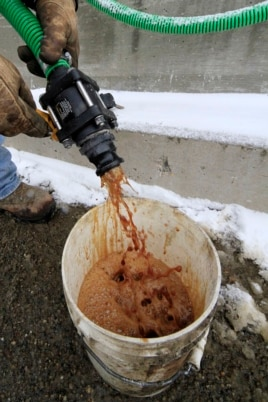In a demonstration, a bucket is filled with beet juice at the Pennsylvania Department of Transportation's Butler, Pa., maintenance facility, Jan. 6, 2014, which is then mixed with road rock salt that is largely ineffective below 16 degrees.