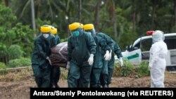 Petugas Pemkot mengenakan alat pelindung diri memakamkan korban COVID-19 di area pemakaman yang disediakan pemerintah di Pulau Sangihe, Sulawesi Utara, 17 April 2020. (Foto: Antara/Stenly Pontolawokang via REUTERS)