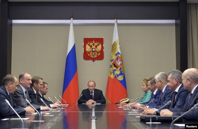Russian President Vladimir Putin, center, meets with Security Council members at the Novo-Ogaryovo state residence outside Moscow, Sept. 30, 2015.