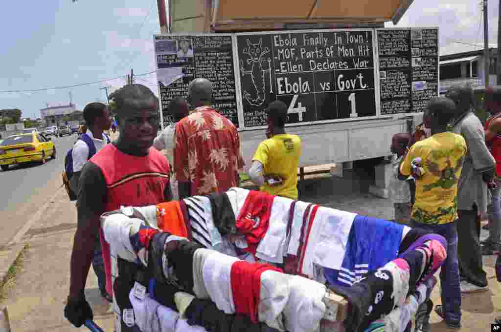 A man sells clothes as he walks past people reading comments on a blackboard that informs the public of current events in Liberia, including information on the Ebola virus, in Monrovia, Liberia, Saturday Aug. 2, 2014.