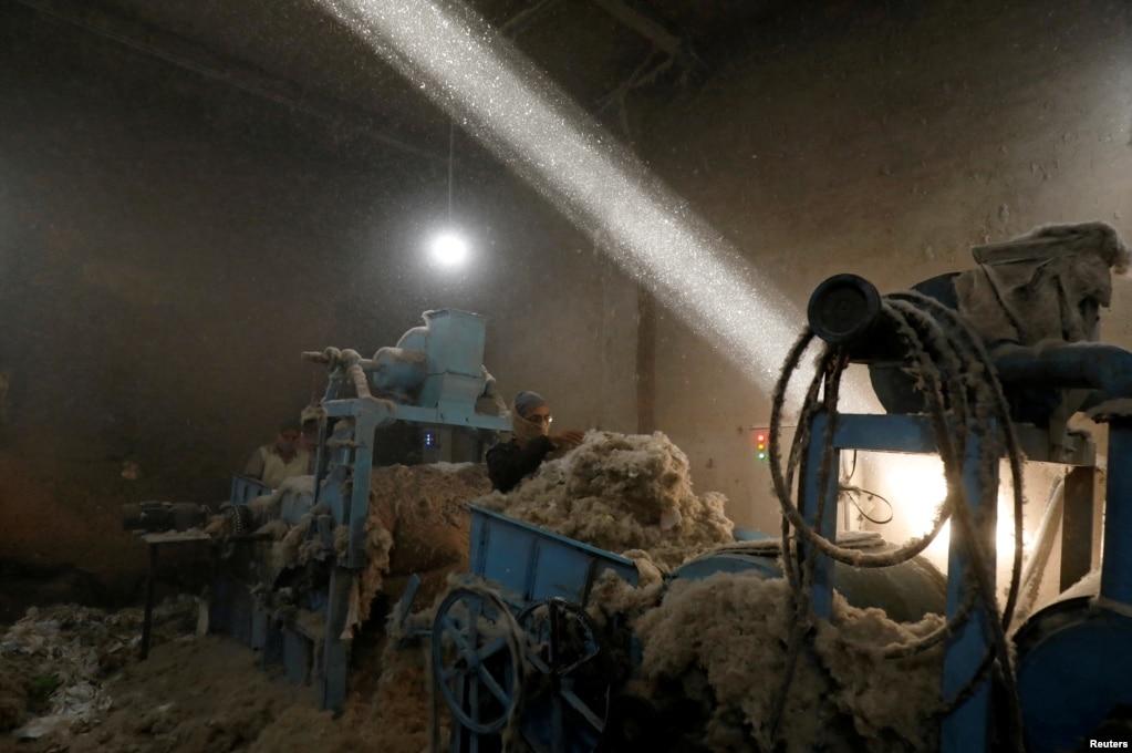 A laborer works at a cotton gin workshop in Peshawar, Pakistan.
