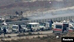 Lực lượng trung thành với Tổng thống Syria ngồi trên xe tăng trong lúc đoàn xe đưa thường dân ra khỏi miền đông Aleppo quay trở lại vùng đất bị bao vây, Syria, 16/12/2016.
