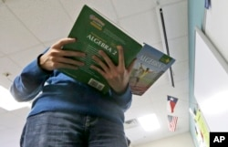 A student holds an Algebra textbook.
