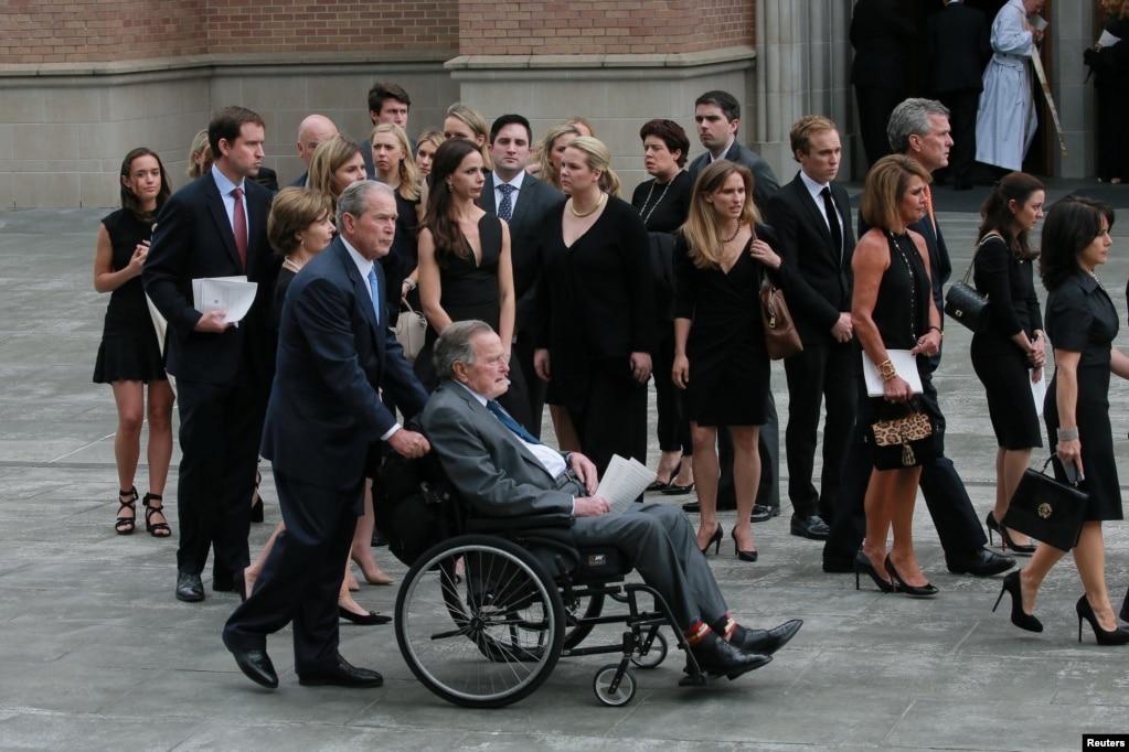 2018年4月21日,在美國德克薩斯州休斯頓的聖馬丁主教教堂,前總統小布什推著坐在輪椅上的父親——前總統老布什參加芭芭拉·布什的葬禮。 四位美國前總統、美國第一夫人和三位前第一夫人等數千名哀悼者向芭芭拉·布什最後告別。