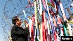 한국 파주시 비무장지대 인근을 방문한 일본인 납북자 가족이 납북 피해자의 송환을 바라는 내용의 리본을 철조망에 걸고 있다. (자료사진)