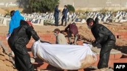 Des fossoyeurs dans un cimetière près de la ville côtière de Sfax, portent des tenues de protection lors de l'enterrement de l'un des 52 migrants africains, décédé en mer lorsque leur bateau a chaviré près des îles Kerkennah en Tunisie, le 15 juin 2020.