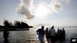 """Grupa ljudi šalje u okean mali splav sa """"ponudama za pretke"""" 19. juna 2005. na plaži Virdžinija Ki u Majamiju, koja je nekada bila označena kao plaža samo za crnce."""
