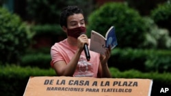 Percibald Garcia uses a microphone to read aloud children's stories amid the high-rise housing complex of Tlatelolco, in Mexico City, Saturday, July 18, 2020.