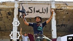 카다피 국가원수 관저의 부서진 동상 위에 올라가 환호하는 반정부군