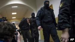 Polisi mengawal Zaur Dadaev, tengah, salah satu dari lima tersangka pembunuh Boris Nemtsov dari sebuah ruangan persidangan di Moskow, Rusia, 8 Maret 2015.