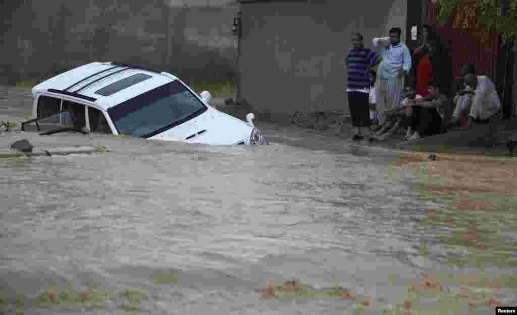 Family members wait for rescue workers after their vehicle was submerged in flood waters on the outskirts of Karachi, August 4, 2013.
