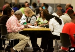 FILE - Job seekers take advantage of banks of tables to fill out their job applications at the Mississippi Employment Expo in Jackson, Miss., March 17, 2009.