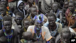 Victims of ethnic violence in Jonglei, state, South Sudan, wait in line at the World Food Program distribution center in Pibor, South Sudan to receive emergency food rations, Thursday, Jan.12, 2012.