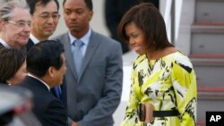 FILE - U.S. first lady Michelle Obama, right, is greeted by an unidentified Japanese official upon her arrival at Haneda International Airport in Tokyo, March 18, 2015.