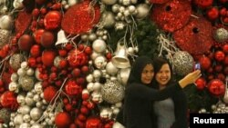 Two women photograph themselves in front of a Christmas tree in a shopping mall in Jakarta.
