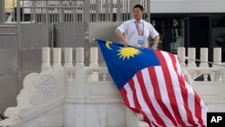 FILE - A worker rolls up a Malaysian national flag after the arrival of the Malaysian delegation at Beijing's International Airport ahead of a Belt and Road forum in Beijing, China, May 12, 2017.
