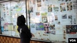 Seorang perempuan muda membaca iklan lowongan kerja menjadi PRT di sebuah pusat perbelanjaan di Kuala Lumpur (foto:dok).