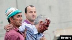 出轨列车的司机弗朗西斯科•加尔松(中间受伤者)2013年7月24日在列车出事后被两人搀扶着往前走
