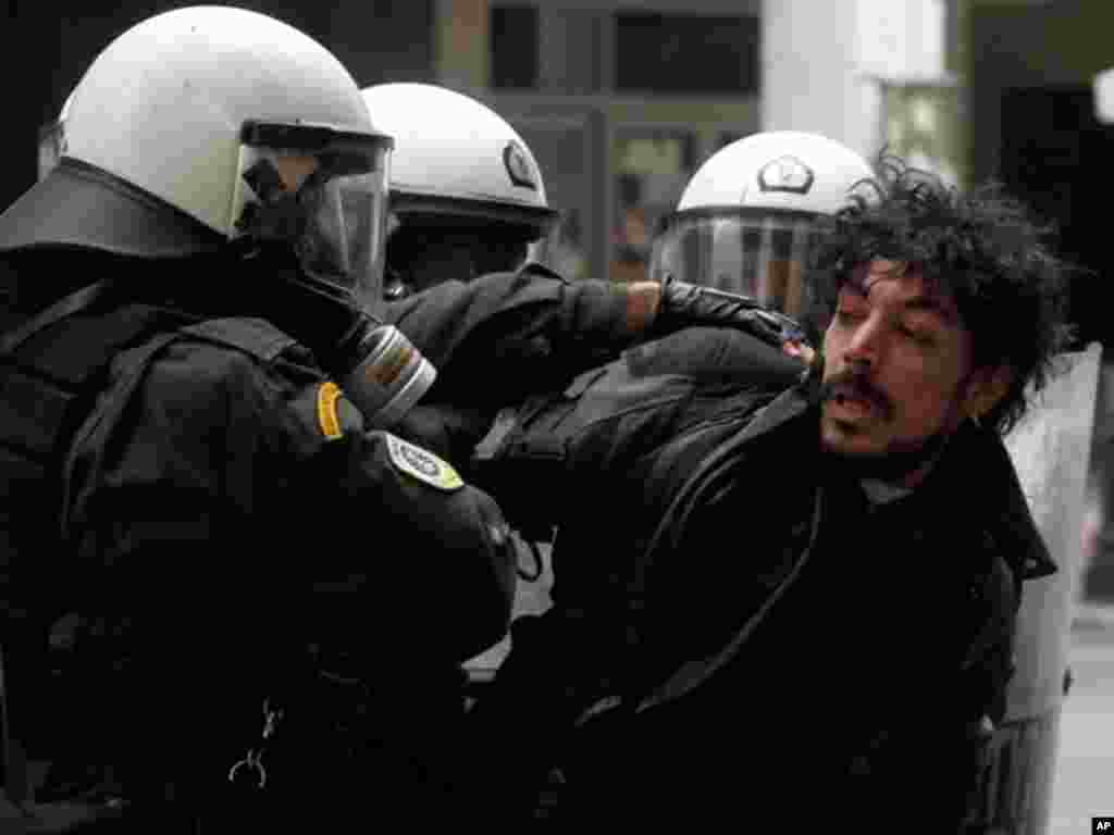 Riot police detain a protester during clashes in Athens, February 10, 2012. (AP)