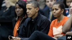FILE - President Barack Obama, with first lady Michelle Obama at his left, checks his BlackBerry as they watch a basketball game in Towson, Maryland, Nov. 26, 2011.