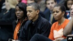 Presiden Barack Obama, di samping ibu negara Michelle Obama, mengecek BlackBerrynya ketika menonton pertandingan bola basket di Towson, Maryland, 26 November 2011. (Foto: dok.)