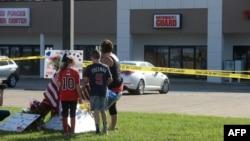 Zach, Zoe dan Melissa Cates meletakkan bunga dekat lokasi penembakan di Pusat Perekrutan Angkatan Bersenjata di Chattanooga, Tennessee (16/7).