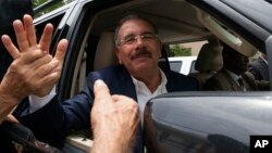 Presiden Republik Dominika, Danilo Medina menyalami pendukungnya setelah memberikan suara dalam pemilu hari Minggu (16/5).