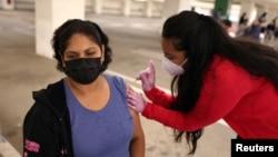 Maria Meza, 43, is given a coronavirus disease (COVID-19) vaccination in Los Angeles, California, U.S., April 12, 2021.