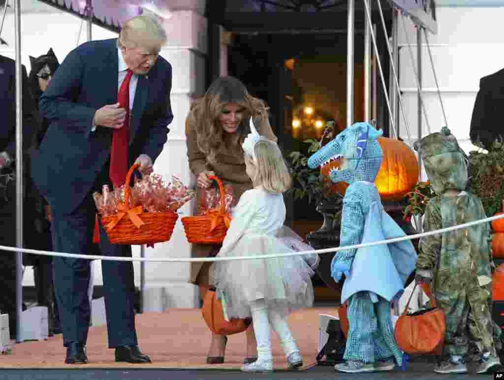Presiden Donald Trump dan Ibu Negara Melania Trump membagikan permen-permensaat menyambut anak-anak di wilayah Washington dan anak-anakdari keluarga militeruntuk merayakan Halloween di South Lawn, Gedung Putih, 30 Oktober 2017.